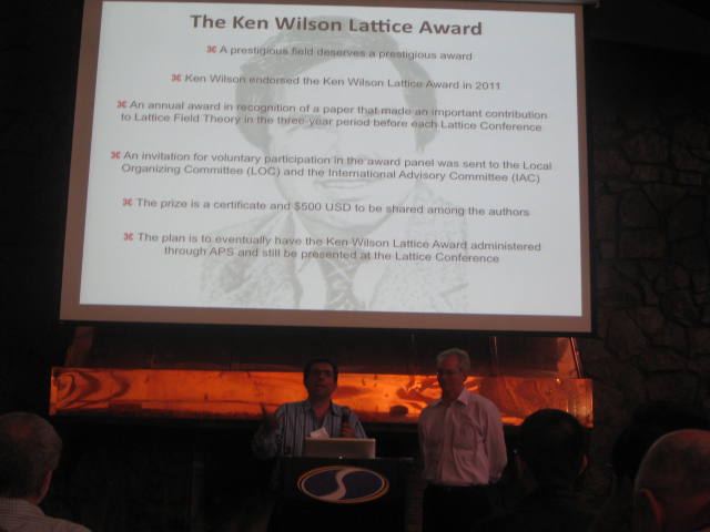 Presenter of the 2011 award with the award slide on a screen behind him.